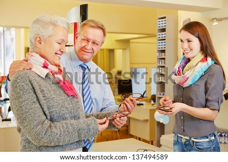 Happy senior couple buying new glasses at optician store - stock photo