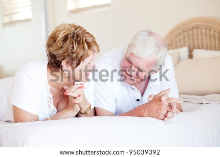 happy senior couple chatting on bed - stock photo