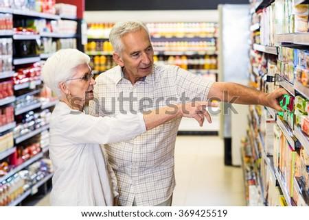 Happy senior couple choosing food at the supermarket - stock photo