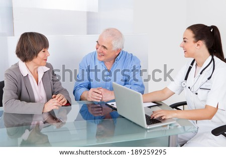 Happy senior couple consulting female doctor in clinic