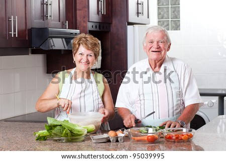 happy senior couple cooking in home kitchen - stock photo