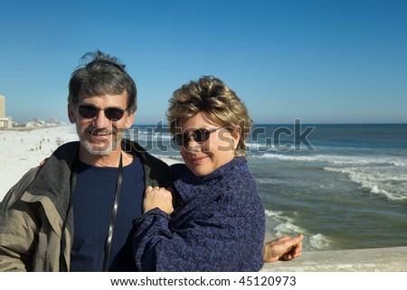 Happy senior couple cuddling at the beach on winter vacation.
