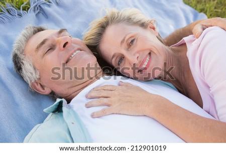 Happy senior couple cuddling on blanket on a sunny day - stock photo