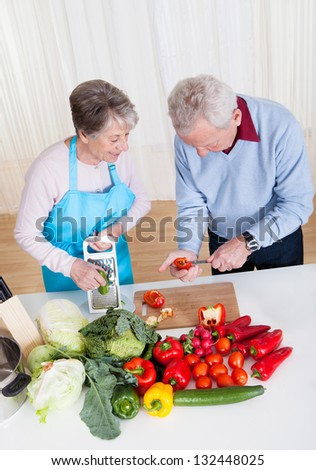 Happy Senior Couple Cutting Vegetables In Kitchen - stock photo