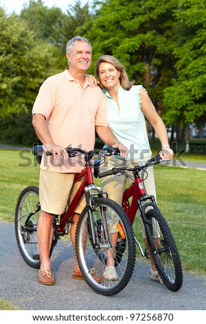 Happy senior couple cycling in the park. Healthy lifestyle. - stock photo