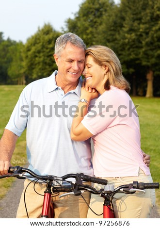 Happy senior couple cycling in the park. Healthy lifestyle.