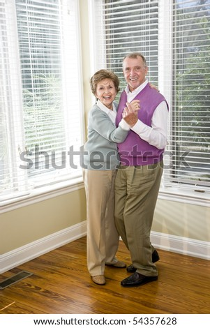 Happy senior couple dancing together in living room - stock photo