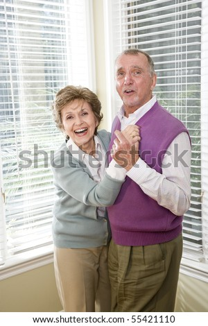 Happy senior couple dancing together in living room