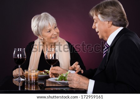 Happy Senior Couple Dining Together With Wine In A Restaurant - stock photo