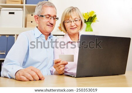 Happy senior couple doing online banking at laptop computer with credit card
