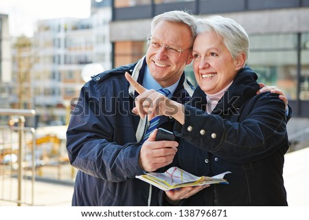 Happy senior couple doing sightseeing tour on city trip with a map - stock photo