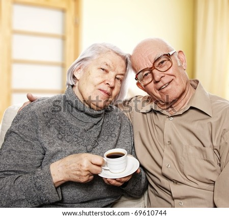 Happy senior couple drinking coffee at home - stock photo