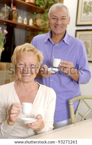 Happy senior couple drinking coffee at kitchen. - stock photo