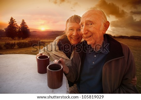 Happy senior couple drinking coffee outside during sunset - stock photo