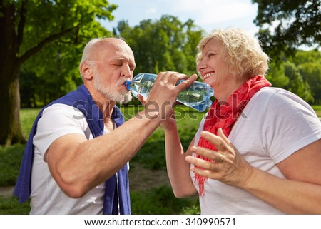 Happy senior couple drinking fresh water in summer