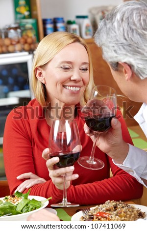 Happy senior couple drinking red wine in a restaurant - stock photo