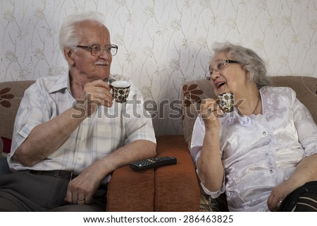 Happy senior couple drinking their morning coffee - stock photo