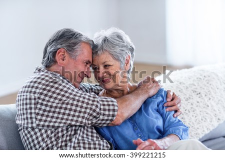 Happy senior couple embracing each other on sofa in living room - stock photo