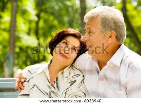 Happy senior couple embracing outdoors. Focus on man. - stock photo
