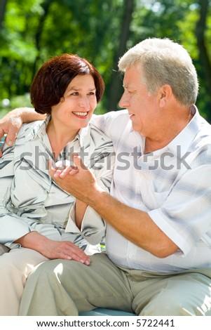 Happy senior couple embracing outdoors. Focus on woman. - stock photo