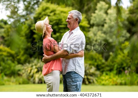 Happy senior couple embracing whiel standing in yard - stock photo