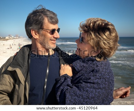 Happy senior couple enjoying themselves at a beautiful beach on their winter or spring vacation. Closeup view of the couple gazing at each other with the beach and ocean in the background. - stock photo