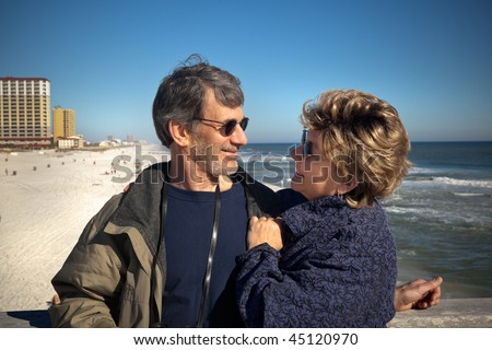 Happy senior couple enjoying themselves at a beautiful beach on their winter or spring vacation. Wide view of Couple gazing at each other with the beach, ocean and hotels in the background. - stock photo