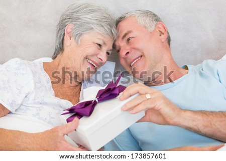 Happy senior couple exchanging gift box while relaxing in bed at home - stock photo