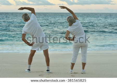 Happy Senior couple exercising in summer on  seashore - stock photo