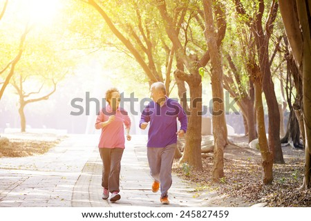 happy Senior Couple Exercising In the Park - stock photo