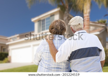 Happy Senior Couple From Behind Looking at Front of House. - stock photo