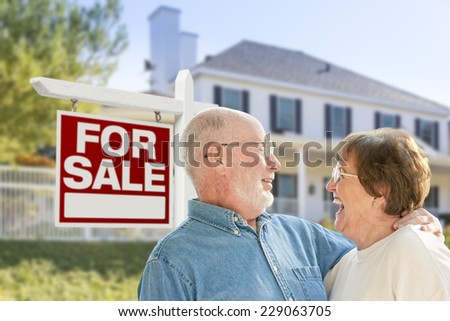 Happy Senior Couple Front of For Sale Real Estate Sign and House. - stock photo