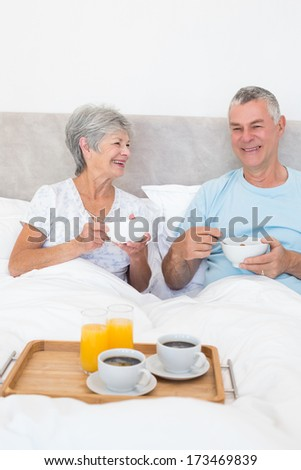 Happy senior couple having breakfast in bed at home