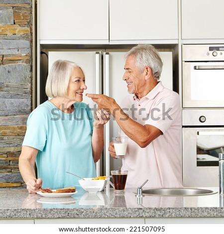 Happy senior couple having breakfast in kitchen with toast and milk - stock photo