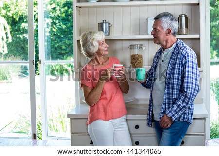 Happy senior couple having coffee in kitchen at home - stock photo