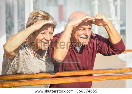 Happy senior couple having fun looking to future - Concept of active playful elderly during retirement - Travel lifestyle with childish funny attitude - Marsala color tone with soft glass reflections - stock photo