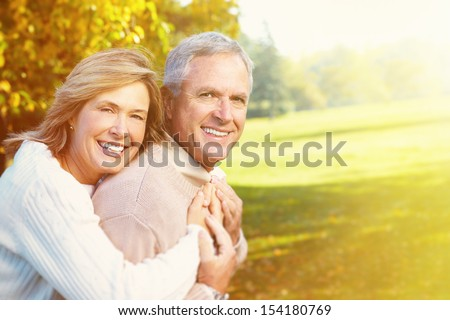 Happy senior couple having fun together in park. - stock photo