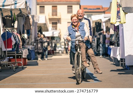 Happy senior couple having fun with bicycle at flea market - Concept of active playful elderly with bike during retirement - Everyday joy lifestyle without age limitation in a spring sunny afternoon - stock photo