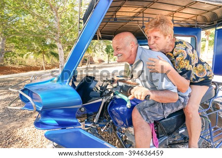 Happy senior couple having fun with tricycle in Philippines travel - Concept of active playful elderly during retirement - Everyday joy lifestyle without age limitation - Warm afternoon color tones - stock photo