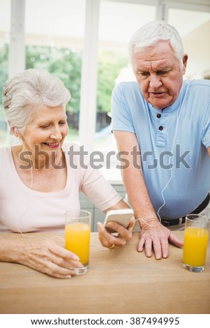 Happy senior couple having juice while listening to music on smartphone