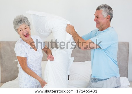 Happy senior couple having pillow fight in bed at home - stock photo