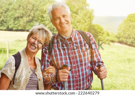 Happy senior couple hiking in summer in nature - stock photo