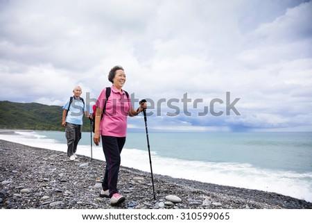 happy senior couple hiking on the coast beach - stock photo