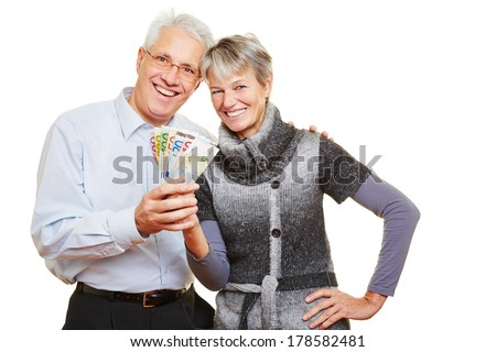 Happy senior couple holding a fan of Euro bills - stock photo