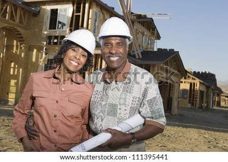 Happy senior couple holding blueprint in front of house under construction - stock photo