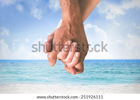 Happy senior couple holding hands against beach scene
