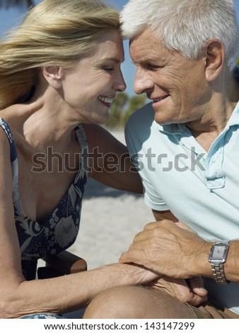 Happy senior couple holding hands on tropical beach - stock photo