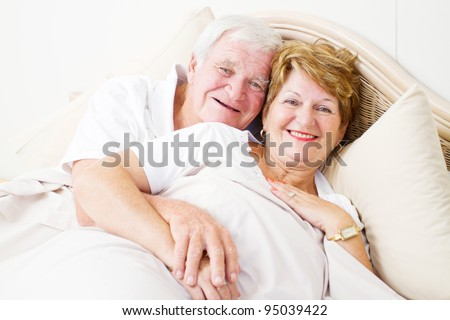 happy senior couple hugging in bed - stock photo