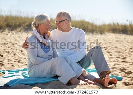 happy senior couple hugging on summer beach - stock photo