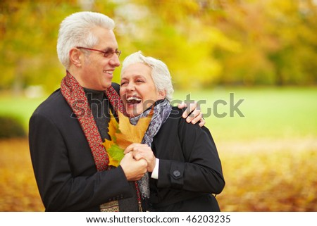 Happy senior couple in an autumn forest - stock photo